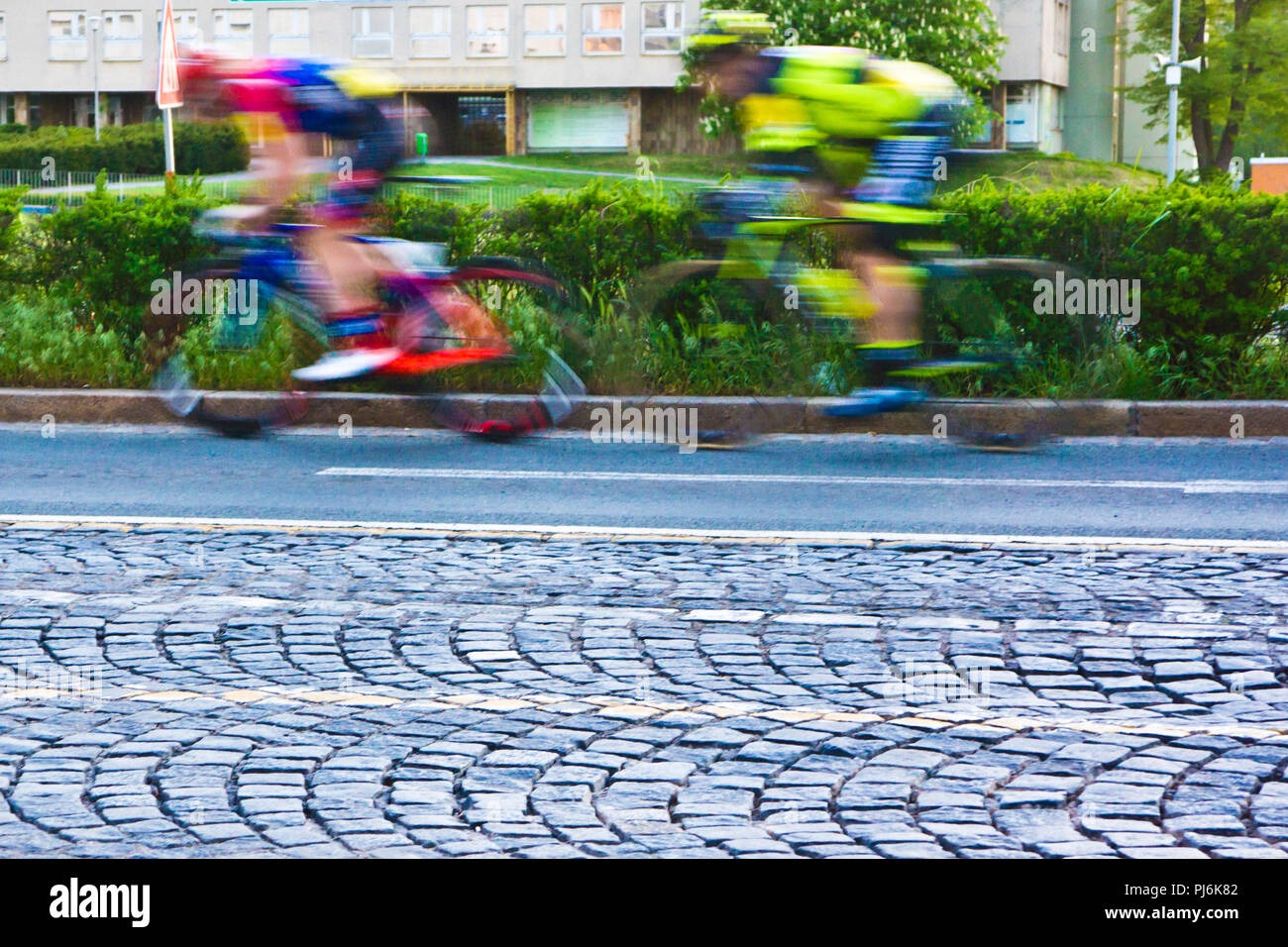cyclists sprinting during a road bicycle racing in the city streets, motion blur effect - Stock Image