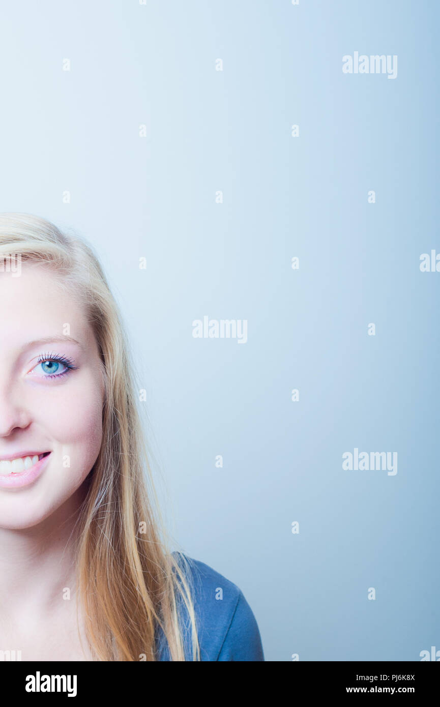 young blonde woman with blue eyes smiling, half face portrait - Stock Image