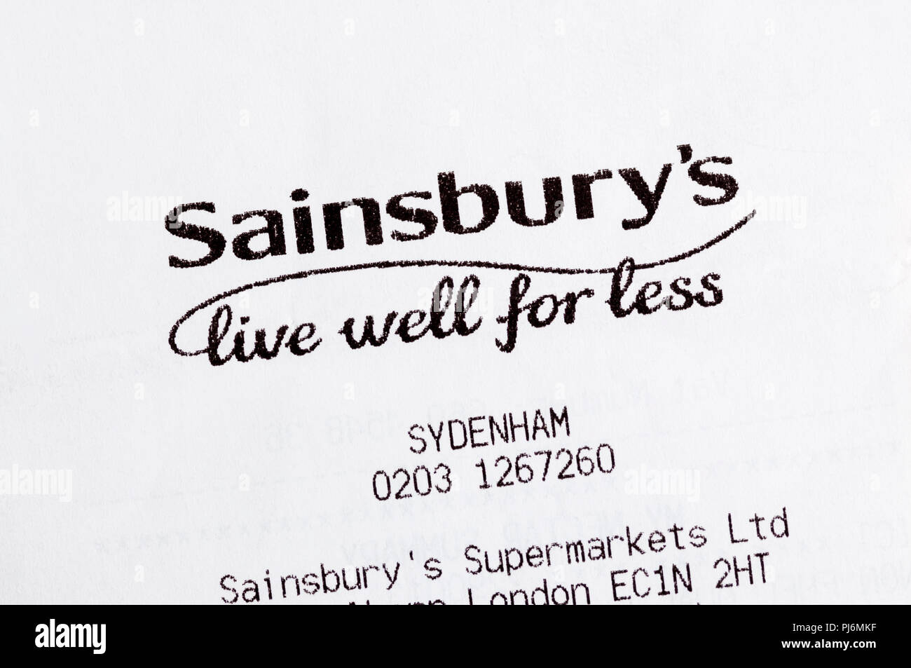 Close-up of Sainsbury's live well for less slogan printed on a till receipt. - Stock Image