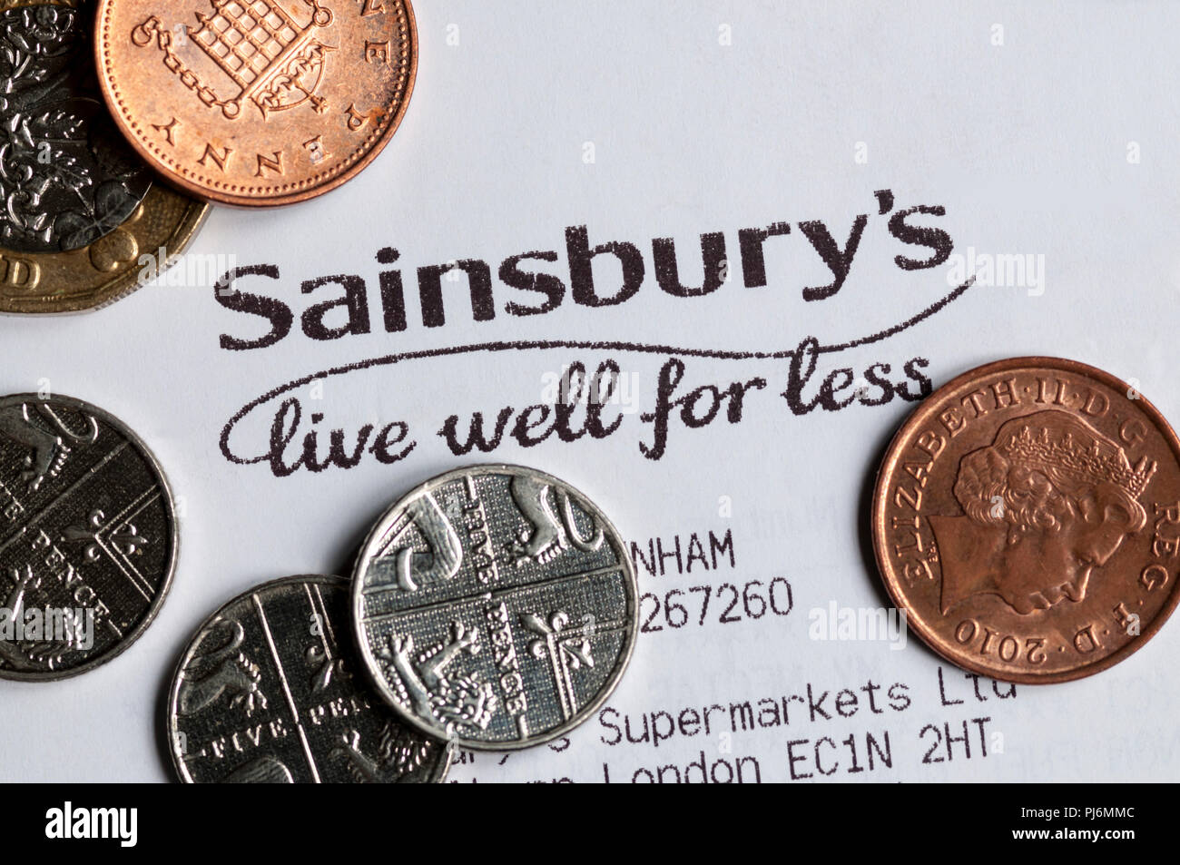 Close-up of Sainsbury's live well for less slogan printed on a till receipt with coins - Stock Image
