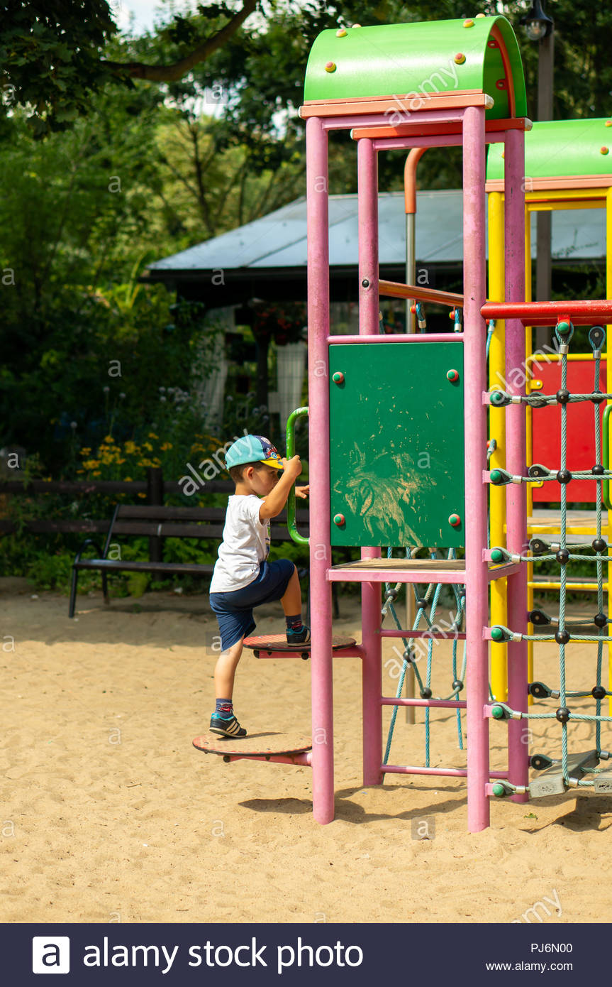 Young boy with shorts and t-shirt climbing a equipment at a playground on a sunny day - Stock Image