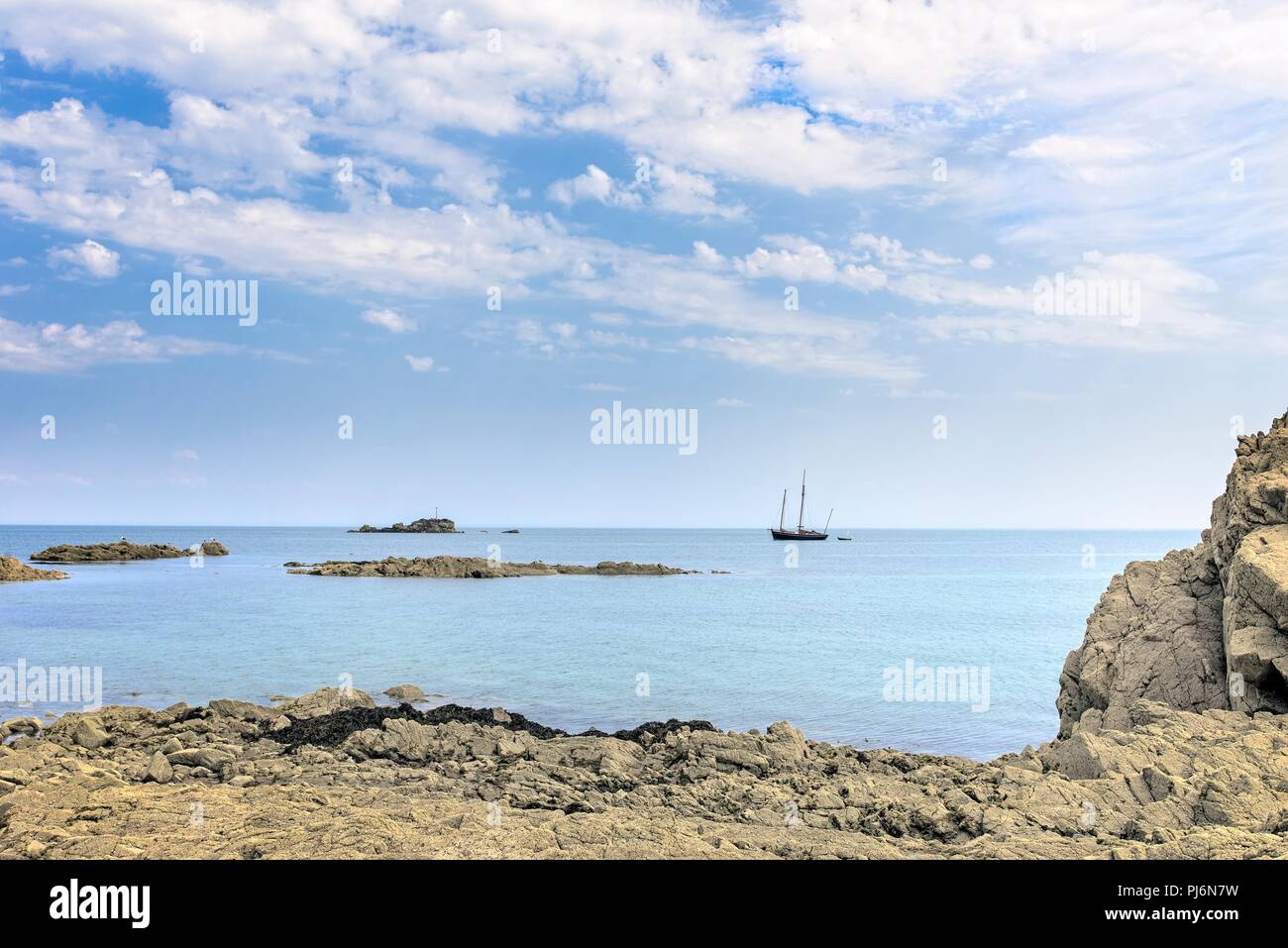 Rocky shoreline at Gorey, Jersey.  A masted boat is moored off shore and a blue, cloud filled sky is above. Stock Photo