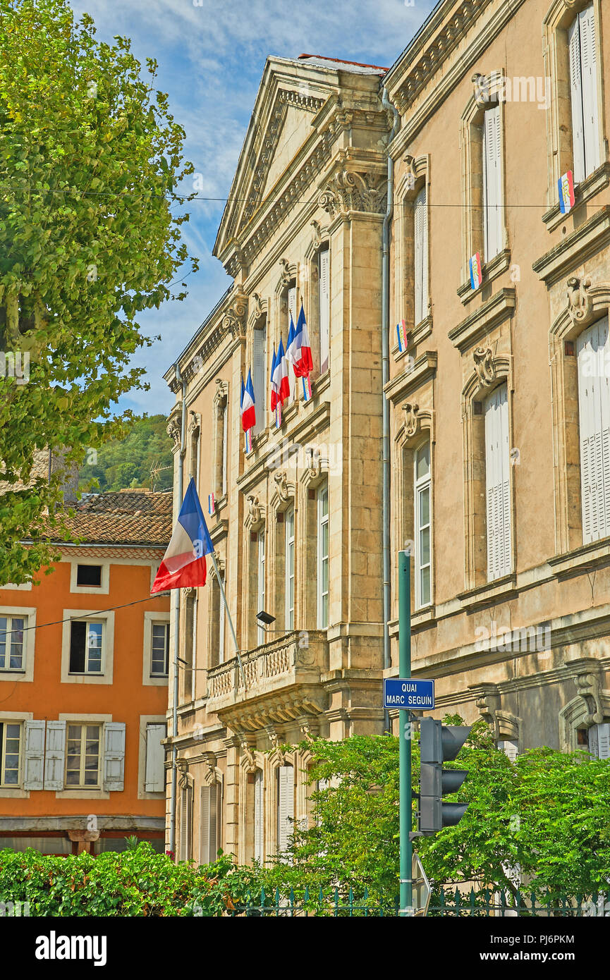 Tournon sur Rhone, Ardeche department, Rhone Alps, France and an ornate stone building with French tricoloure flags flying. Stock Photo