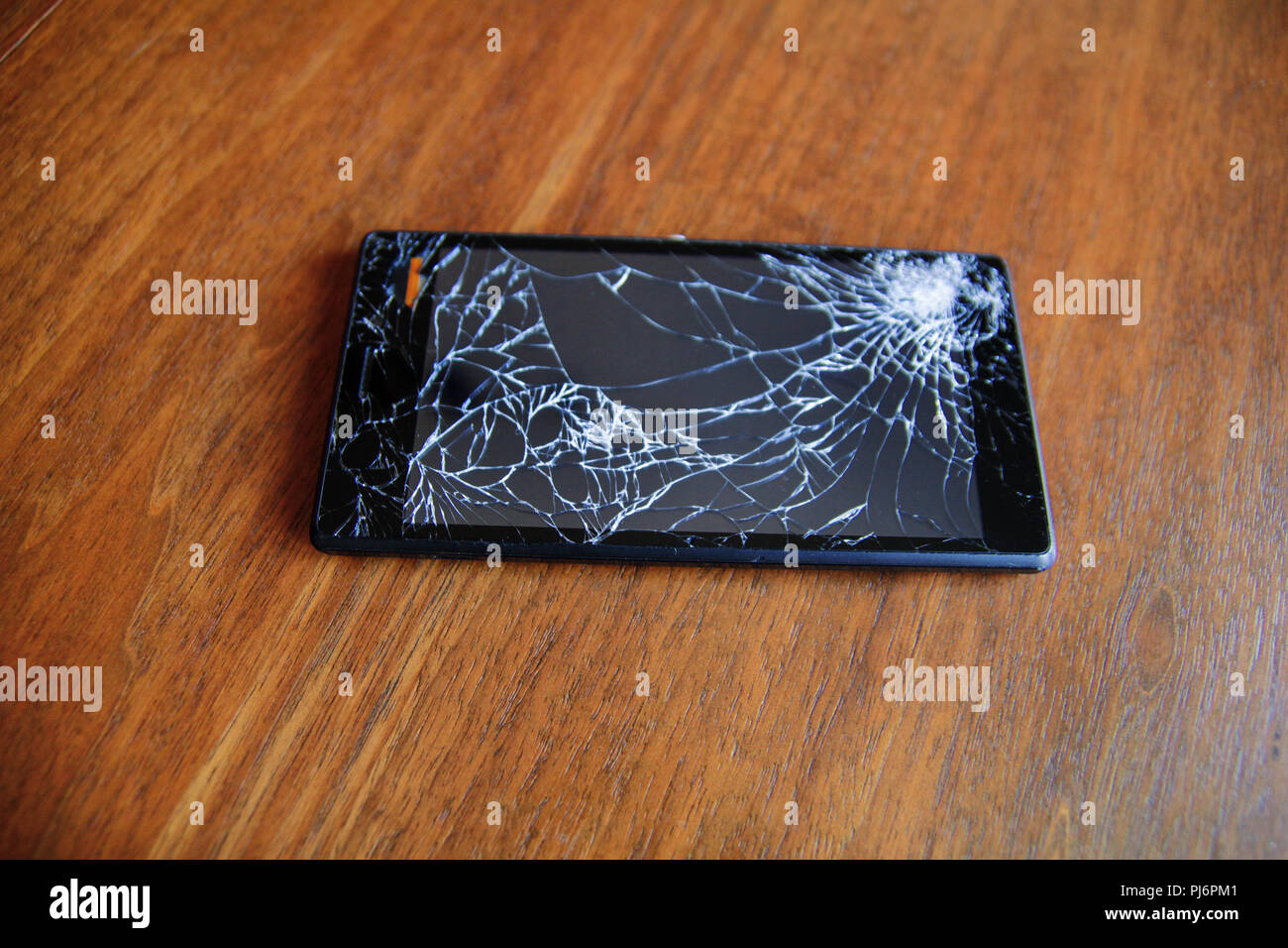Modern mobile smart phone display with broken cracked glass screen on a wooden table, close up. - Stock Image