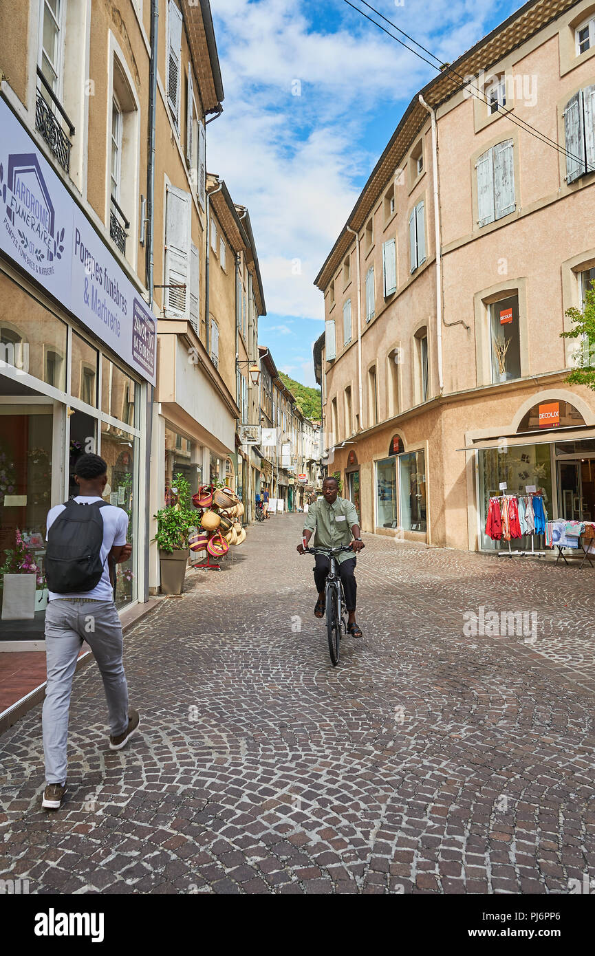 Tournon sur Rhone, Ardeche, Rhone Alps, France a man riding a bike and a man walking through the town centre Stock Photo