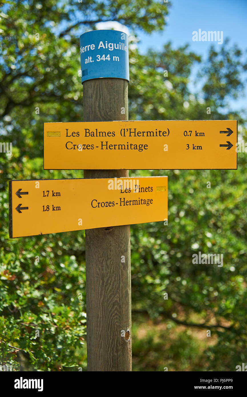 Yellow fingerpost signs on a timber post on the hillside above Tain L'Hermitage in the Drome department, Rhone Alps region, France Stock Photo