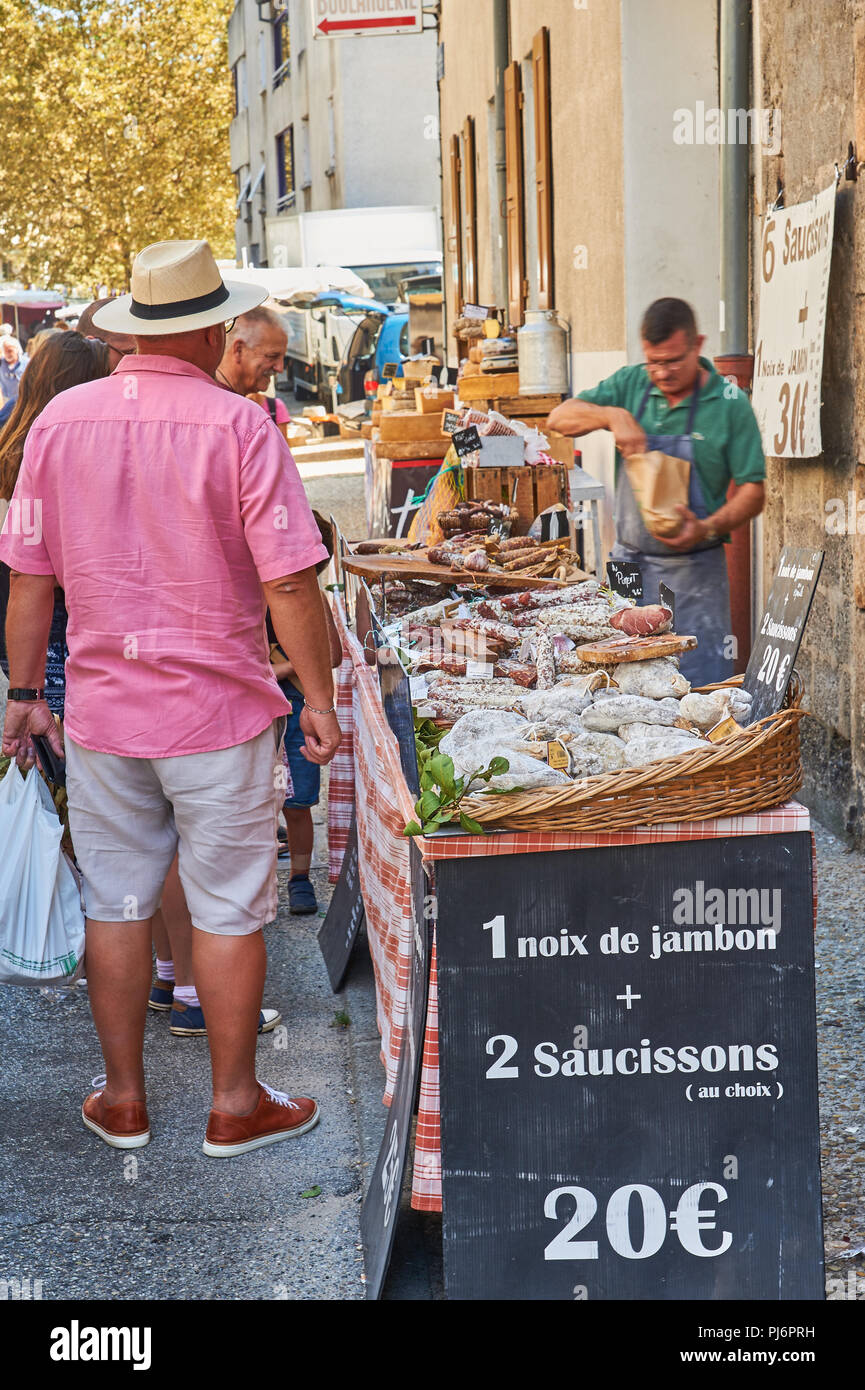 Market trader selling meats during the market at Lamastre, Ardeche, Rhone Alps, France Stock Photo