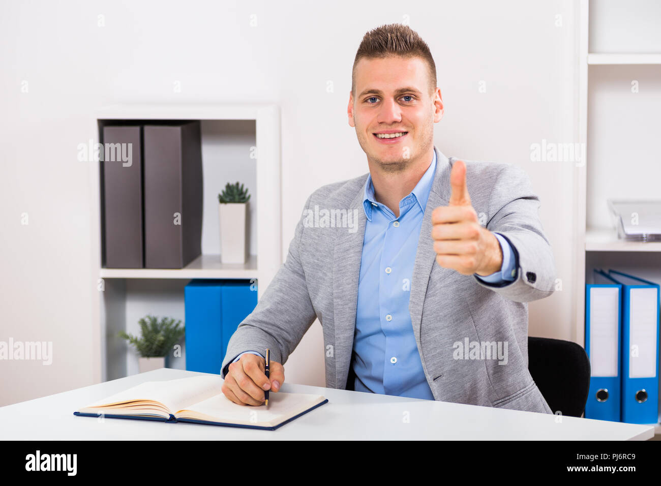 Businessman sitting in his office,working and showing thumb up. - Stock Image