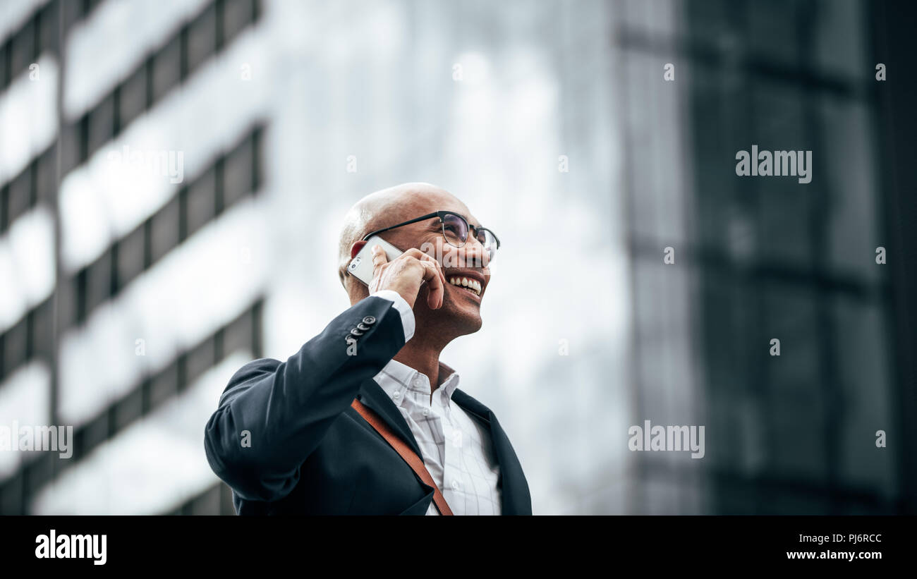 Man in formal clothes wearing office bag walking on street while talking on mobile phone. Smiling businessman talking over cell phone while commuting  - Stock Image