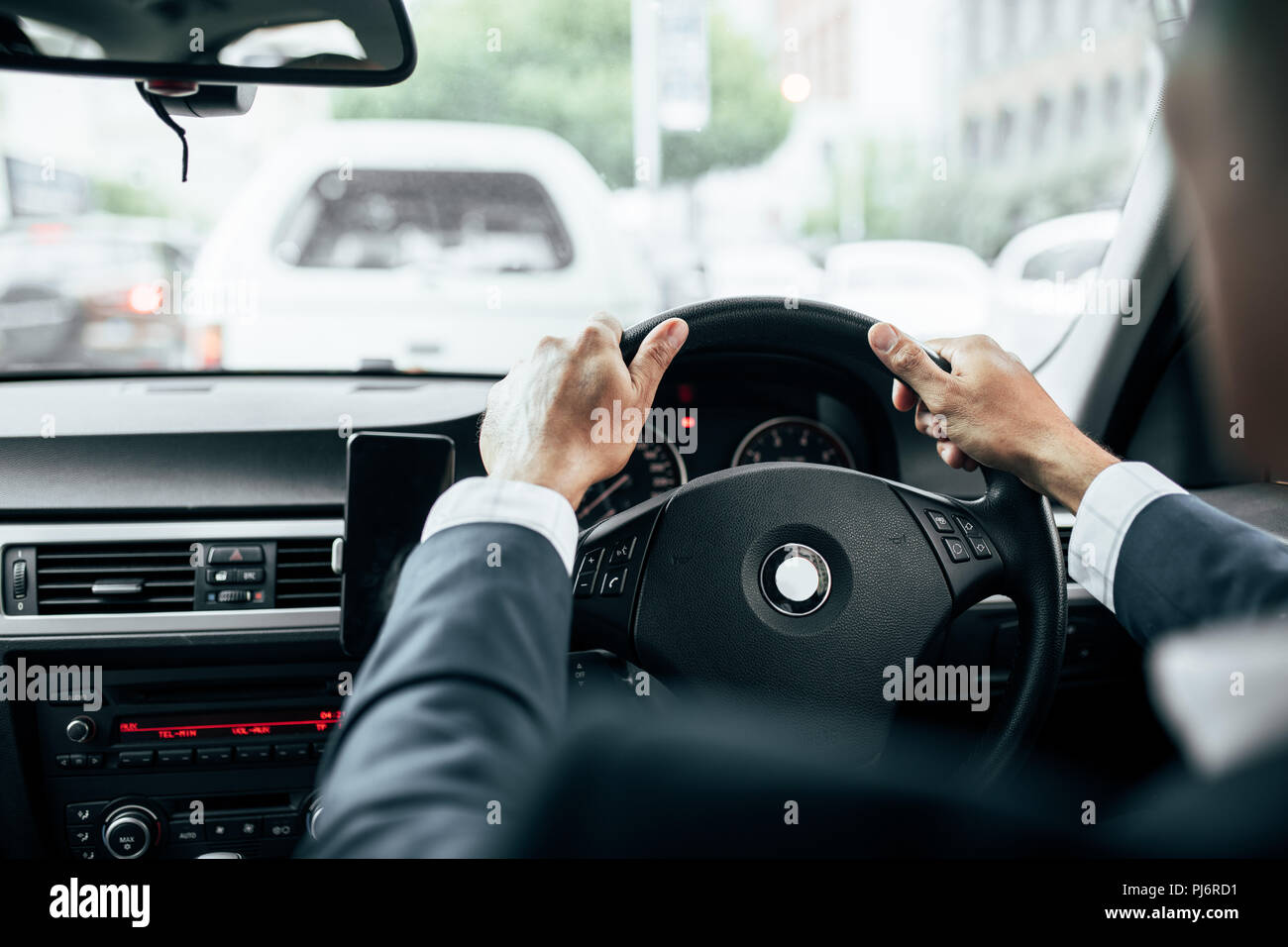 Rear view of man in formal clothes holding the steering wheel of his car with both hands. Businessman driving car with mobile phone clipped to dashboa - Stock Image