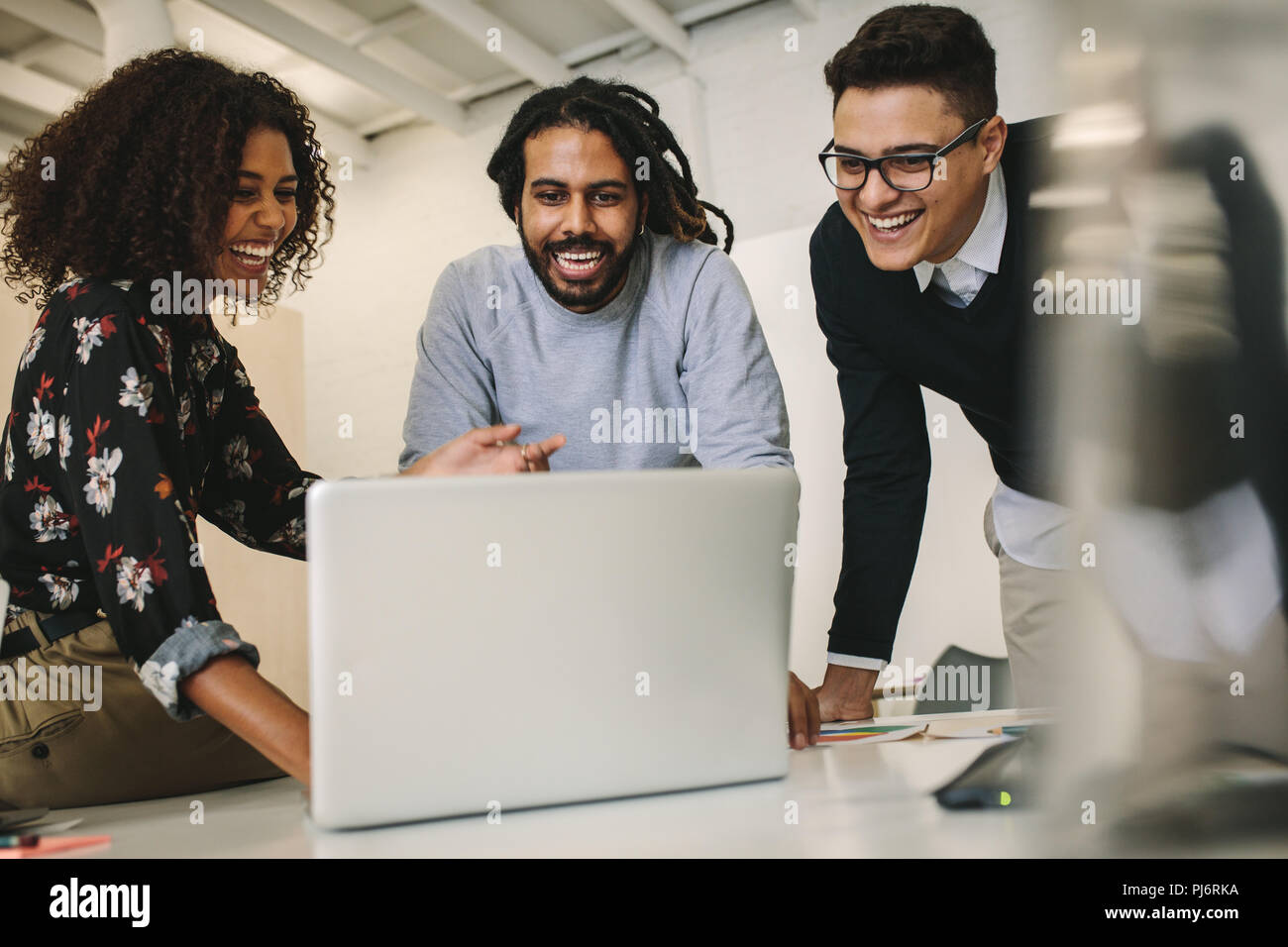 Business colleagues looking at a laptop computer and laughing. Office mates enjoying their work and having fun in office. - Stock Image