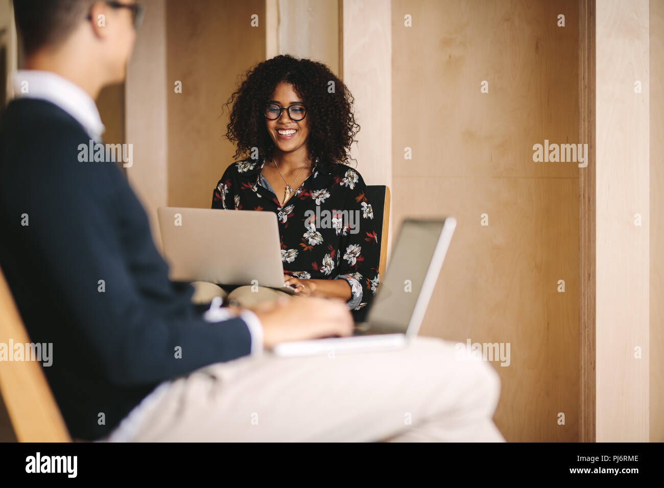 Smiling woman entrepreneur working on laptop sitting on chair with a businessman sitting in front. Office colleagues working on laptops sitting on cha Stock Photo