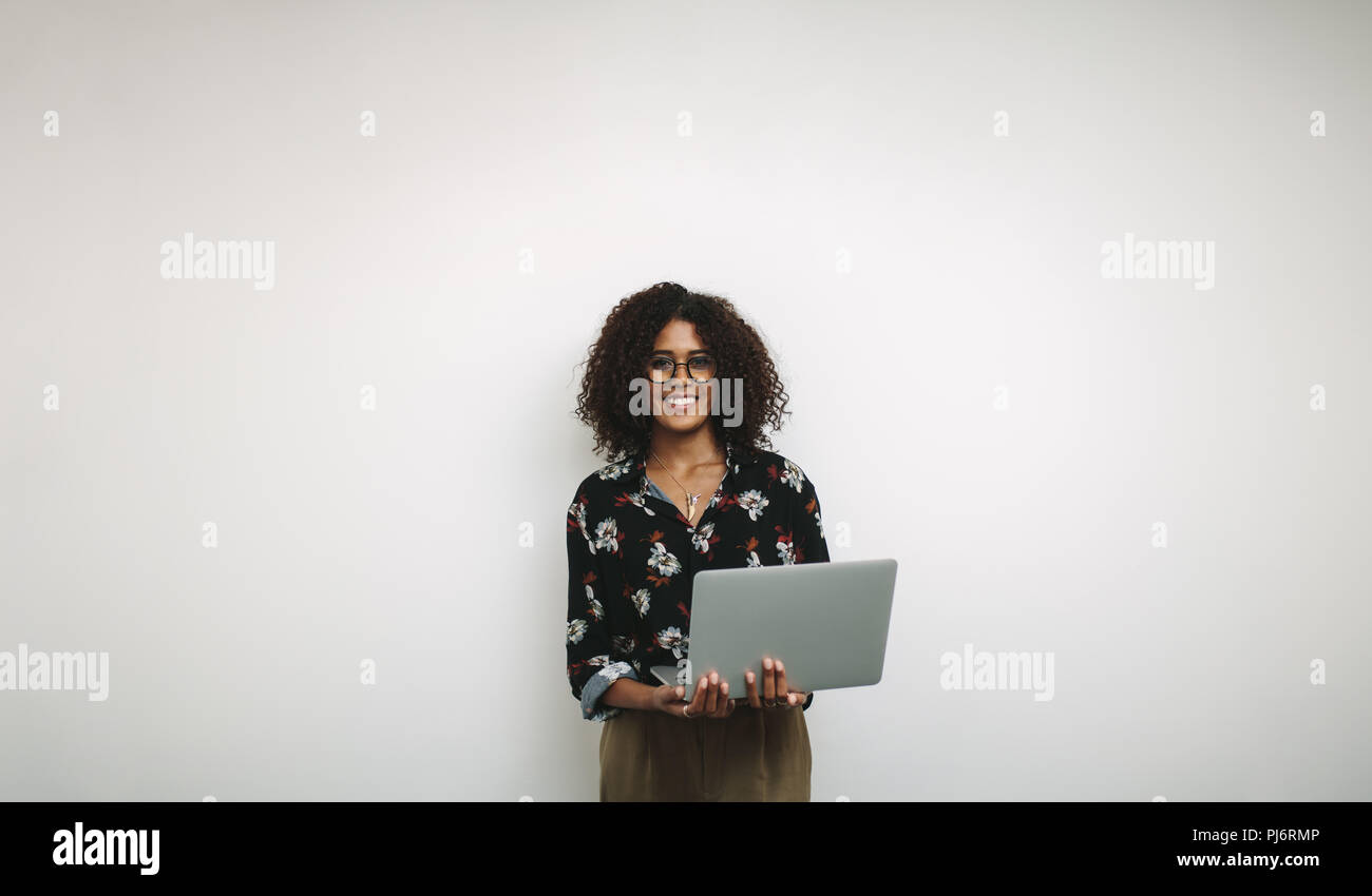 Smiling woman entrepreneur holding a laptop standing against a white background. Portrait of a businesswoman standing with an open laptop. Stock Photo