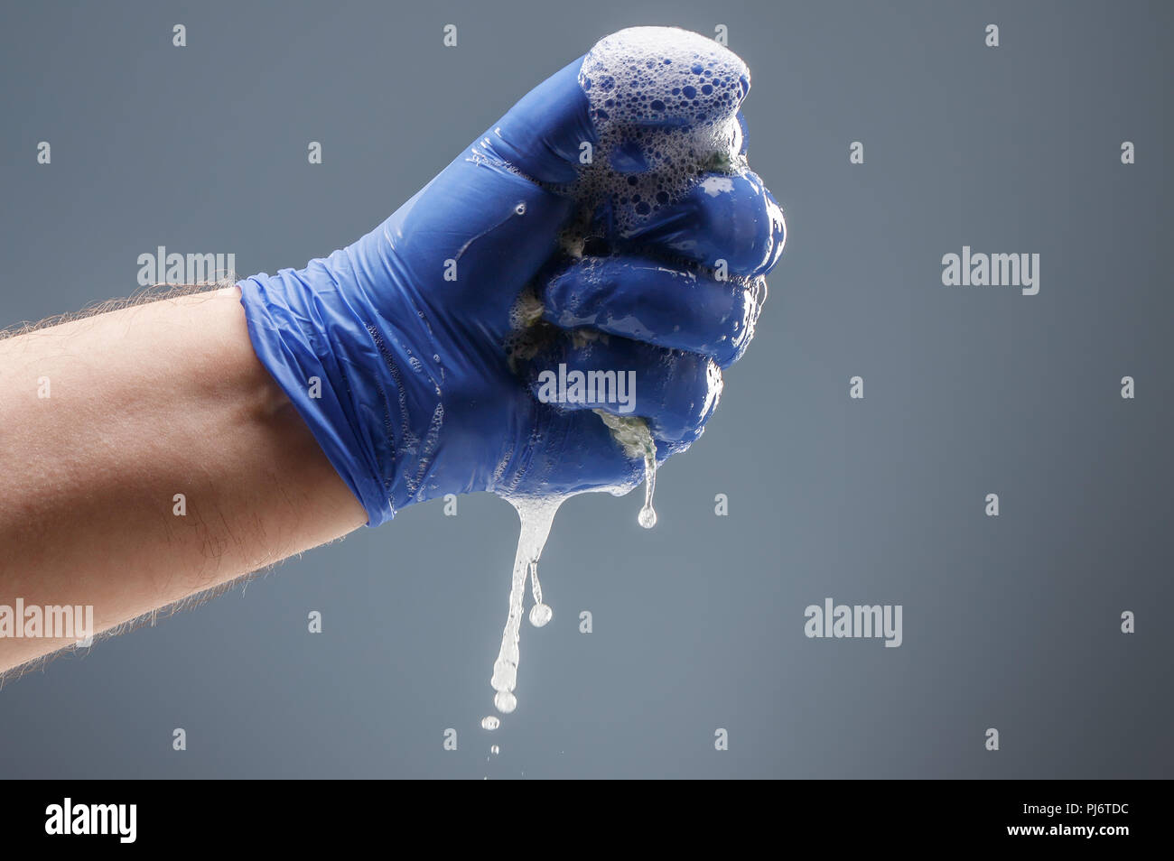 Male hand in blue glove with dripping foam - Stock Image