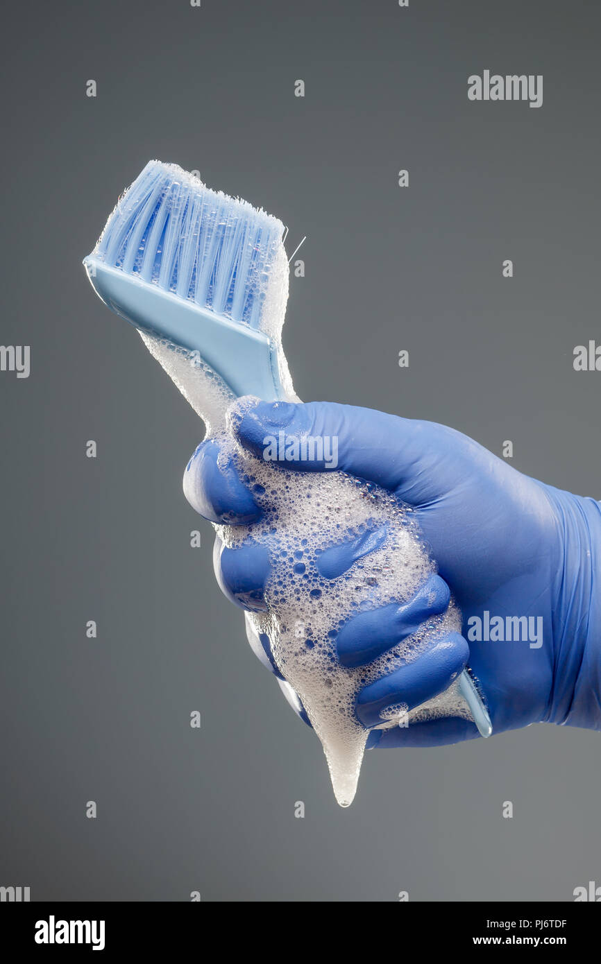A man's hand in a blue glove holds a brush for cleaning with a dripping foam - Stock Image