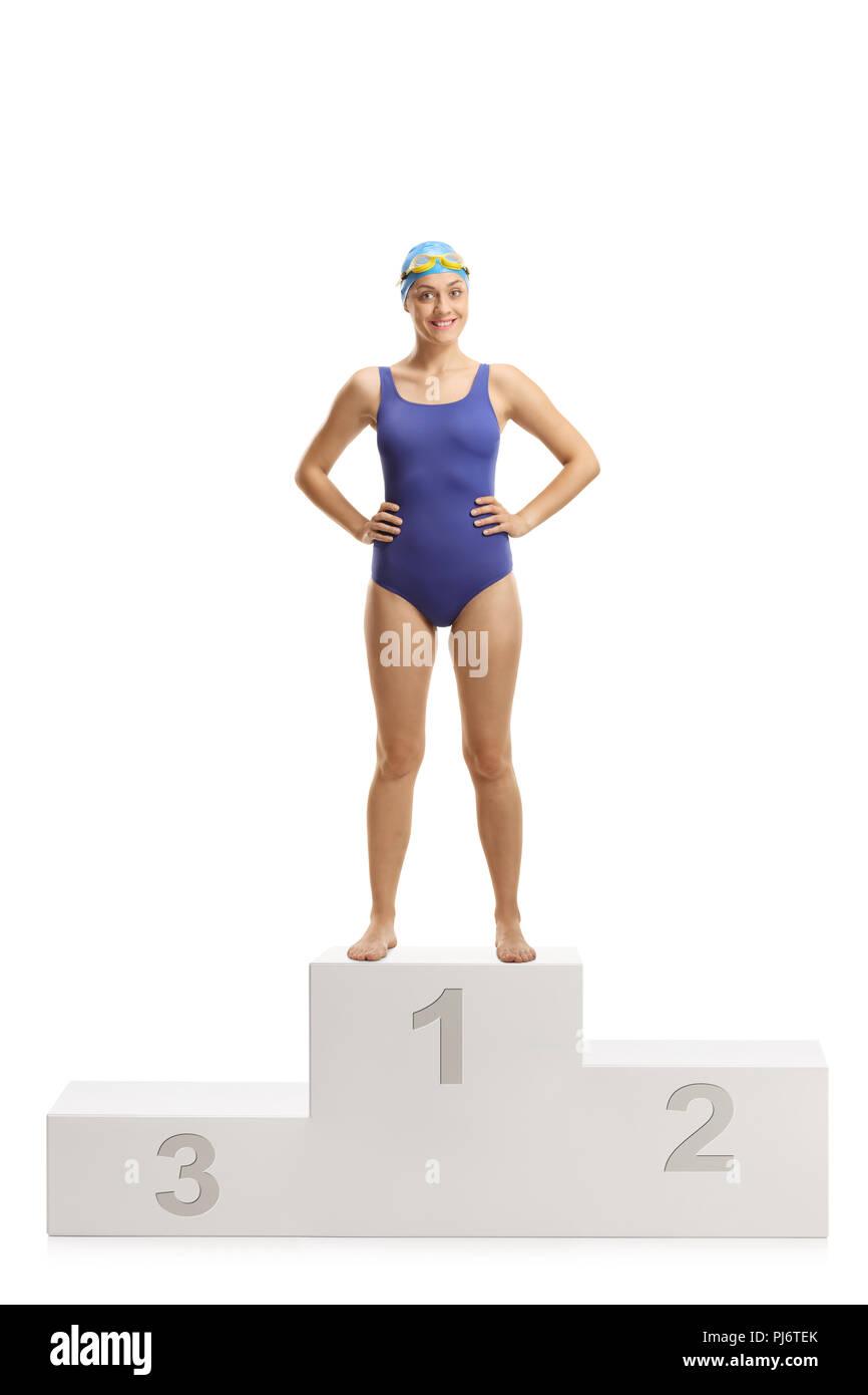 Full length portrait of a female swimmer at a winner's pedestal isolated on white background - Stock Image
