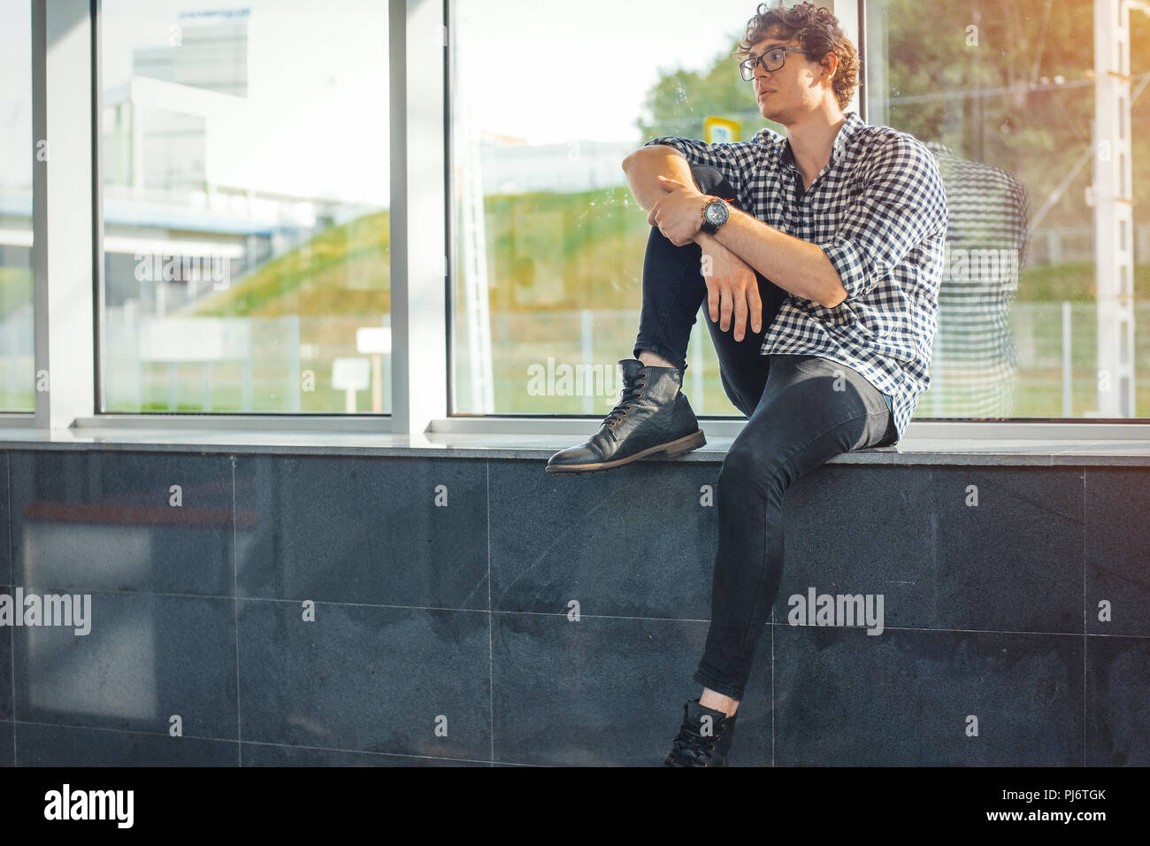 Distant plan of young man sitting next to big windows at metro station. - Stock Image
