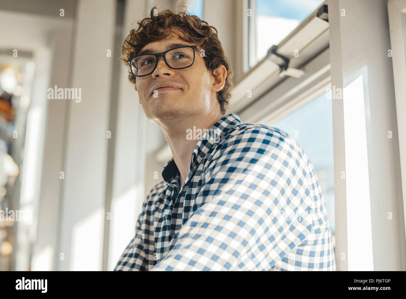 Close up of young man sitting next to big windows at metro station. - Stock Image