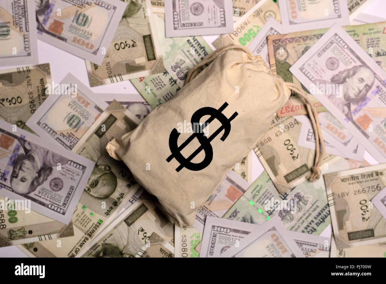 US Dollar Bag Against Rupees And Dollar Paper Currency Stock Photo