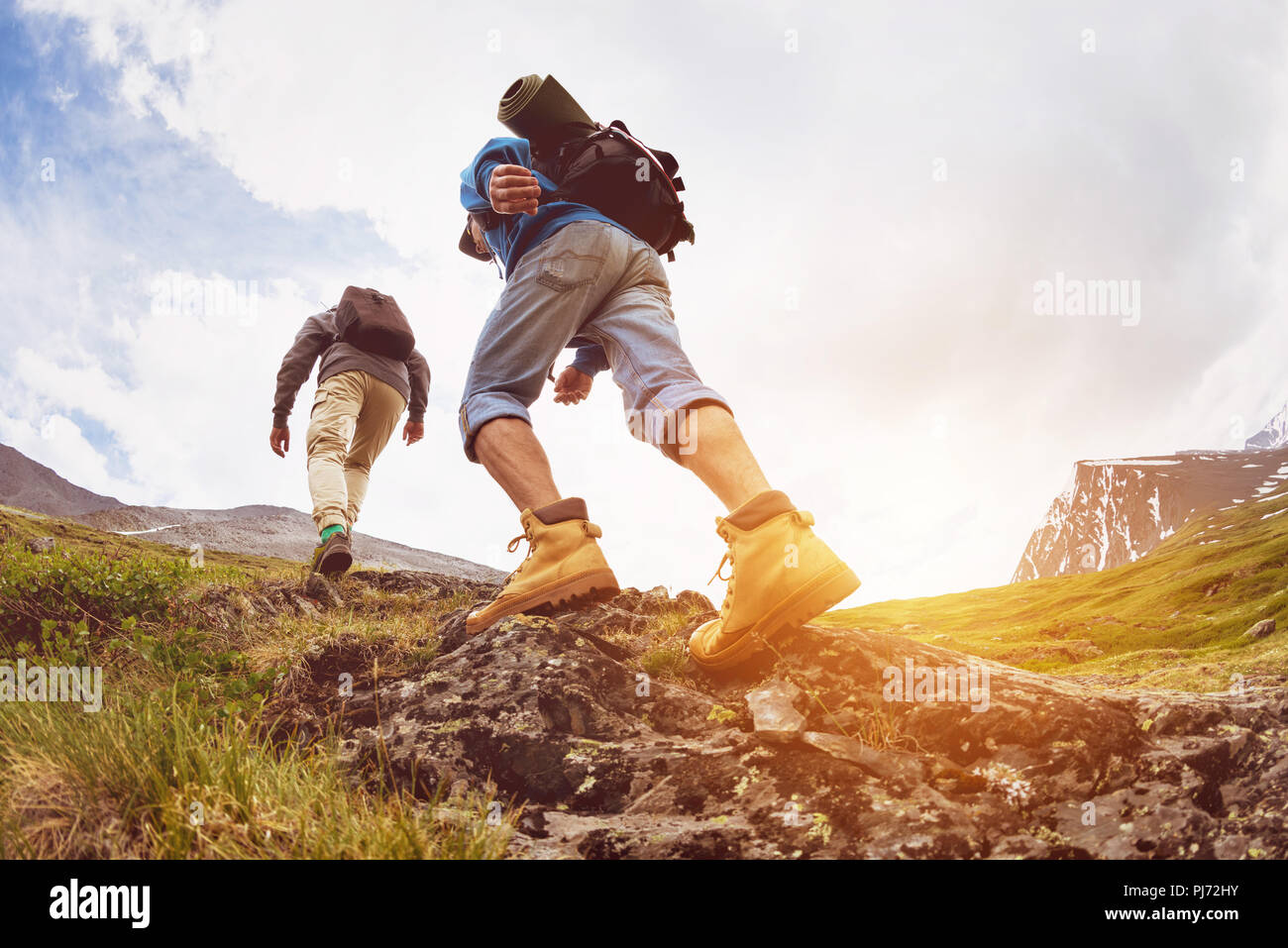 Trekking concept two tourists walking mountains - Stock Image