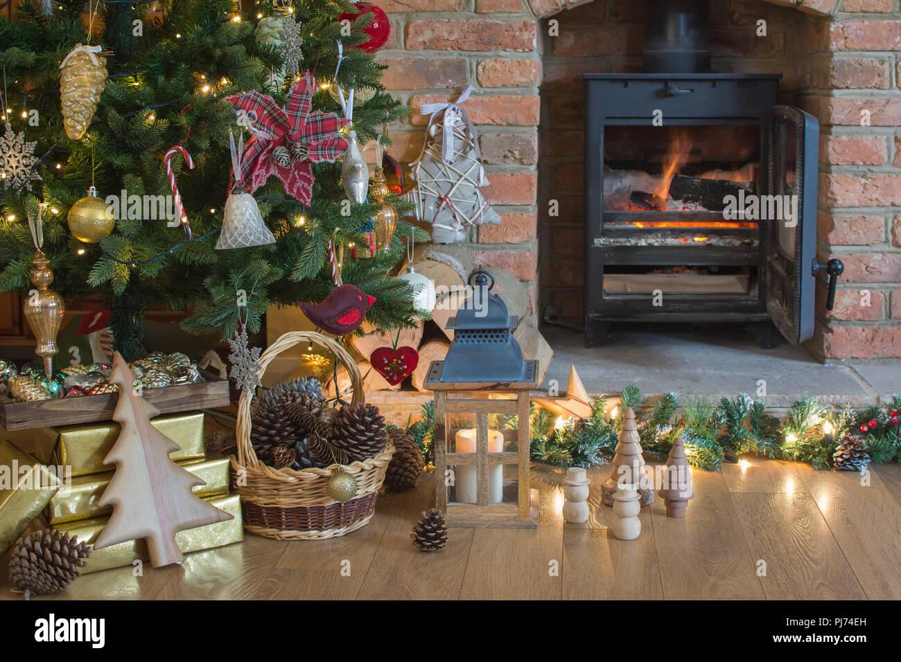 beautiful christmas setting decorated lit up christmas tree with baubles and ornaments fireplace with woodburner lantern stars and garlands sele