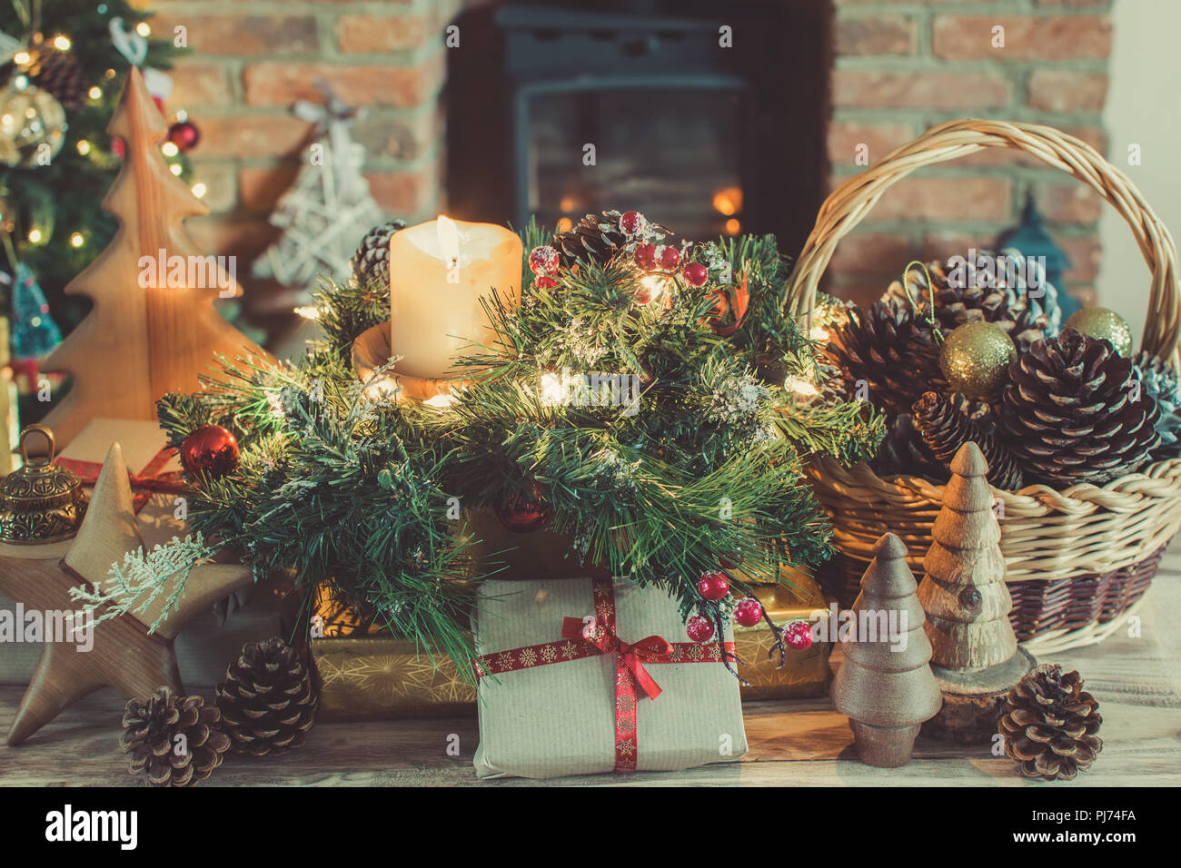 cosy christmas composition presents and decorations on the table in front of the fireplace with woodburner lit up christmas tree with baubles and or