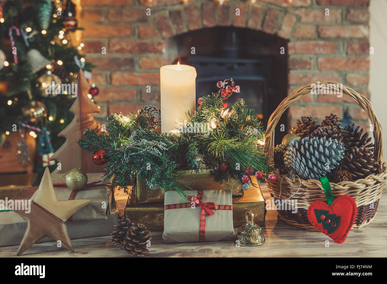 christmas scene presents and decorations on the table in front of the fireplace with woodburner lit up christmas tree with baubles and ornaments and