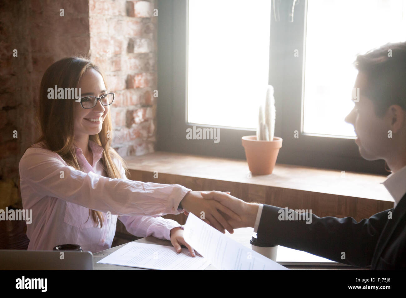 Smiling young man and woman handshake, successful deal - Stock Image