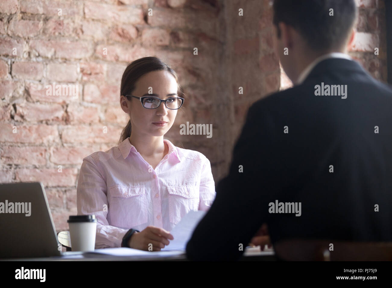 Serious young HR manager woman interviewing male candidate - Stock Image