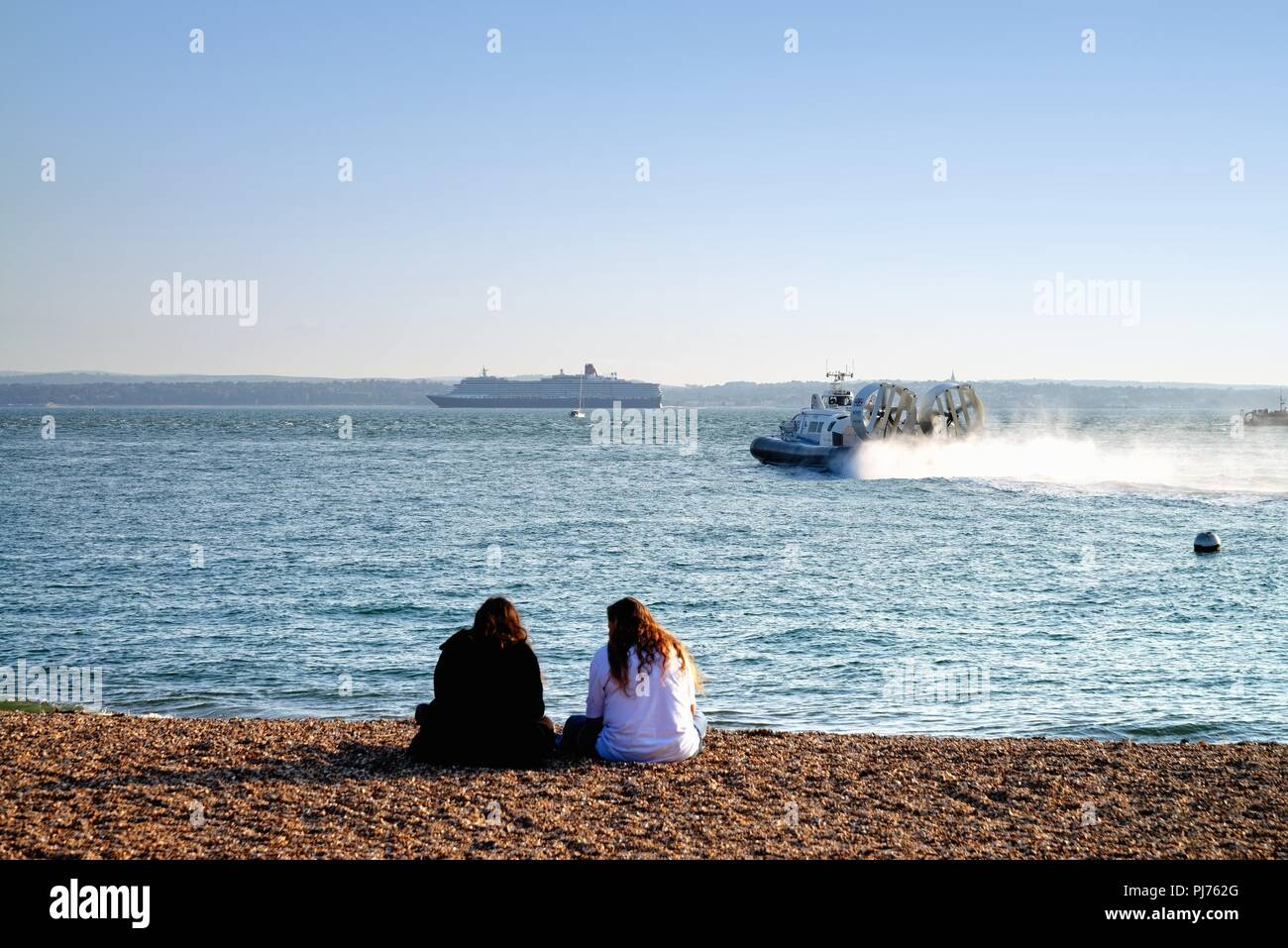 Two young ladies sitting on beach with a passenger hovercraft  in foreground and the cruise liner Queen Victoria sailing past Spithead Portsmouth UK Stock Photo
