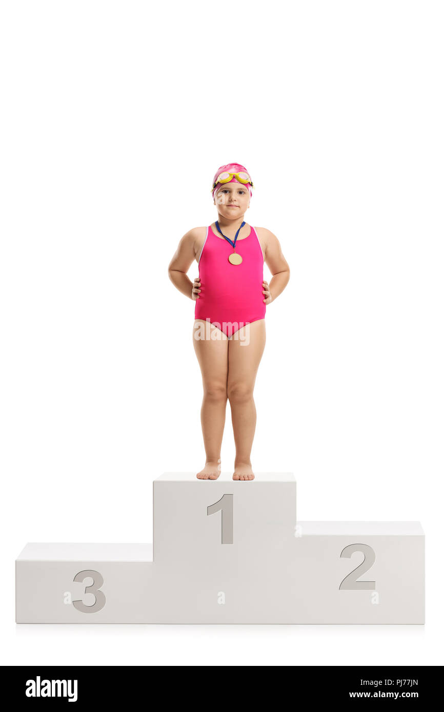 Little girl swimmer with a gold medal standing on a winner's podium isolated on white background - Stock Image