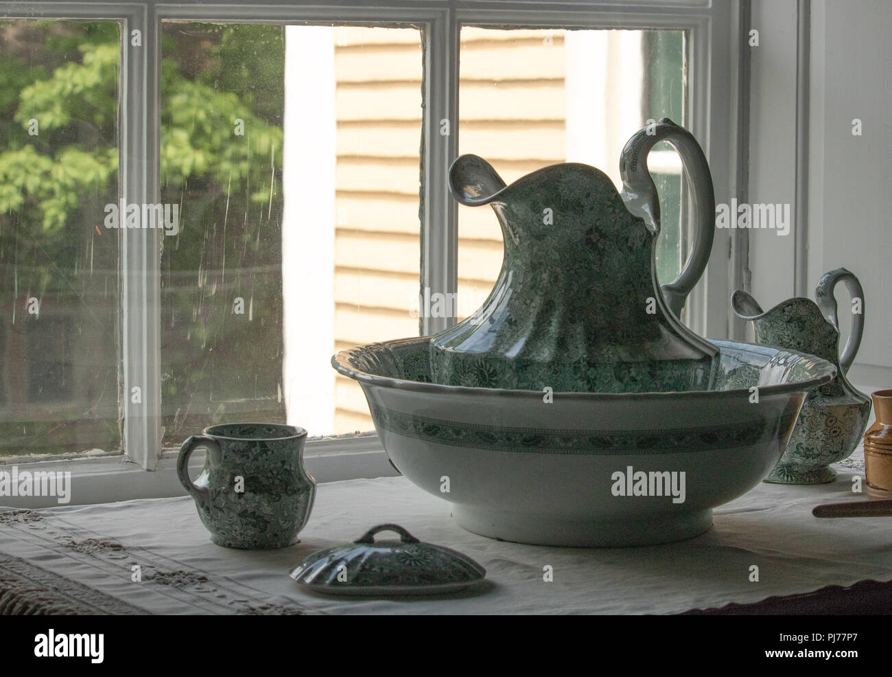 Antique pitcher and bowl from 1800s sitting on washstand, romantic vintage Victorian elegance Stock Photo