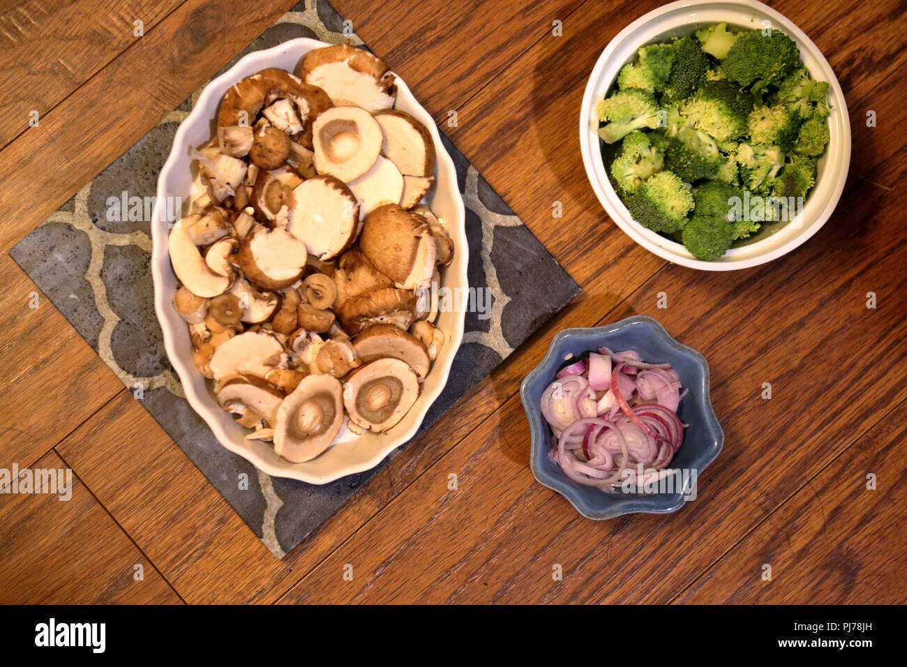 Sliced mushrooms, sliced red onion, and broccoli ingredients ready to add to a fresh supper dish and cook Stock Photo