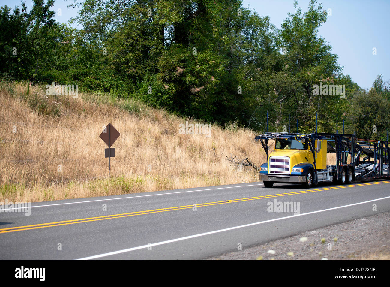 Specialized empty yellow big rig car hauler semi truck with two-tiered semi trailer going to load cars on winding road with hill and green trees Stock Photo