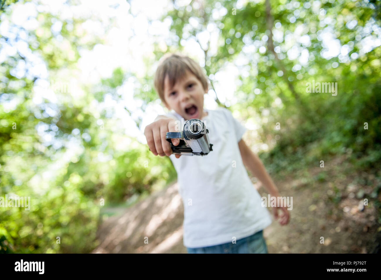 angry threatening little caucasian kid aiming gun at camera shouting outdoors - Stock Image