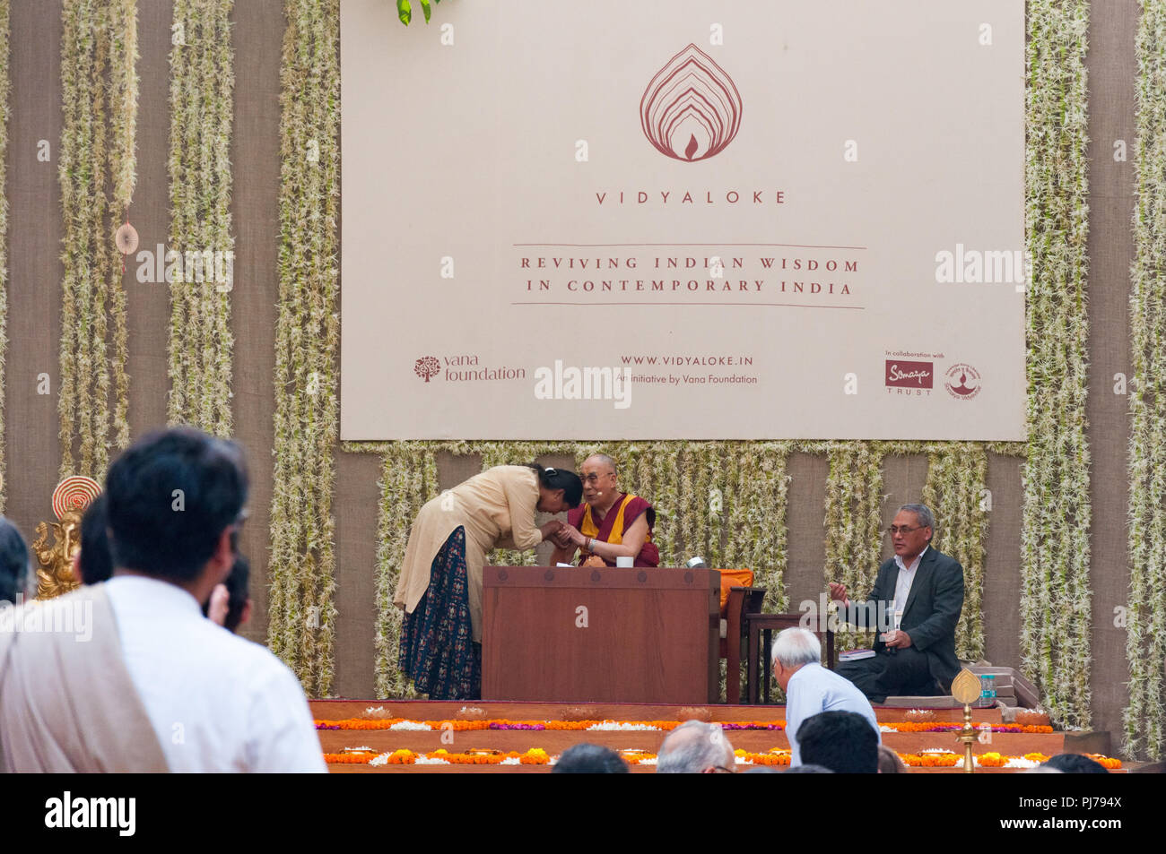 MUMBAI, INDIA – December 10 2017: The 14th Dalai Lama, the Buddhist religious head, blesses a woman on the stage at a lecture event. - Stock Image