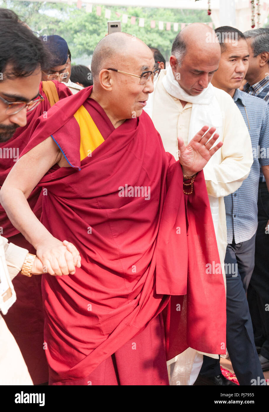 MUMBAI, INDIA – December 10 2017: His Holiness the 14th Dalai Lama waves to people as he is escorted by volunteers at a spiritual lecture event at Som - Stock Image