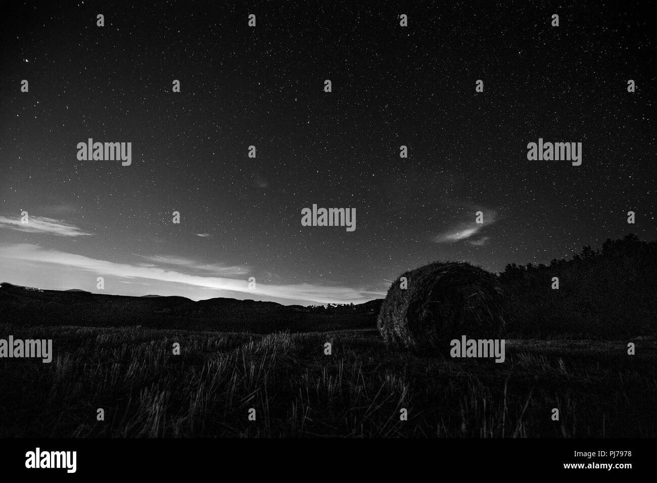 Beautiful view of starred night sky with clouds over a cultivated field with hay bale - Stock Image