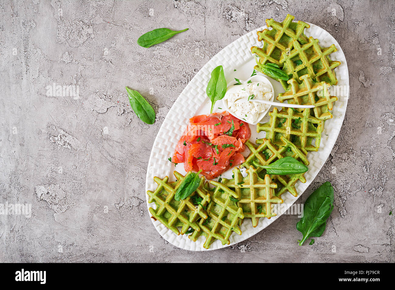 Savory waffles with spinach and cream cheese, salmon in white plate. Tasty food. Top view. Flat lay - Stock Image
