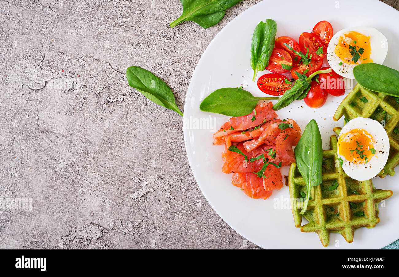 Savory waffles with spinach and egg, tomato, salmon in white plate. Tasty food. Top view. Flat lay - Stock Image