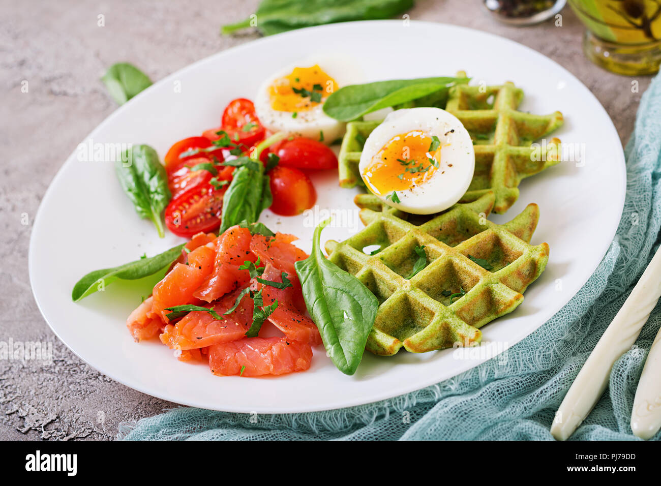 Savory waffles with spinach and egg, tomato, salmon in white plate. Tasty food. - Stock Image