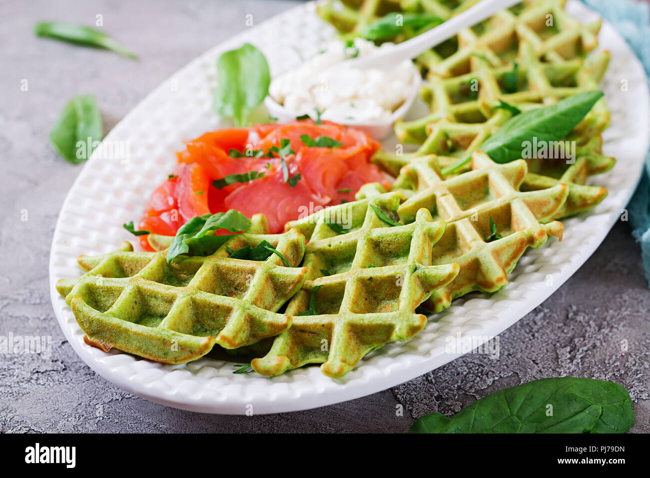 Savory waffles with spinach and cream cheese, salmon in white plate. Tasty food. - Stock Image