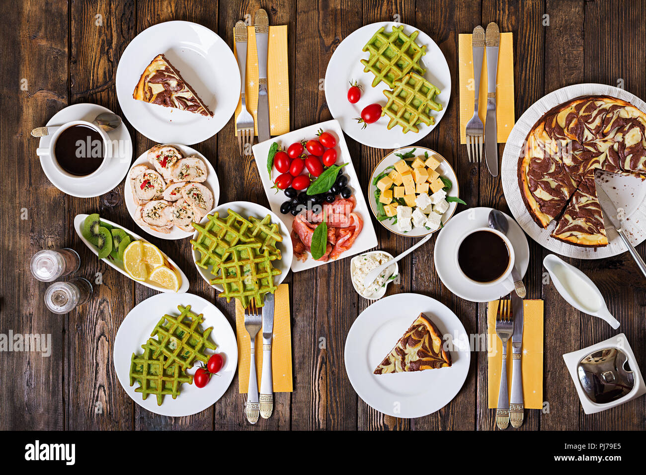Breakfast food table. Festive brunch set, meal variety with spinach waffles, salmon, cheese, olives, chicken rolls and cheesecake. Top view. Flat lay - Stock Image