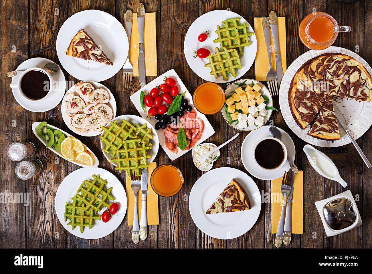Breakfast food table. Festive brunch set, meal variety with spinach waffles, salmon, cheese, olives, chicken rolls and cheesecake. Top view. Flat lay Stock Photo