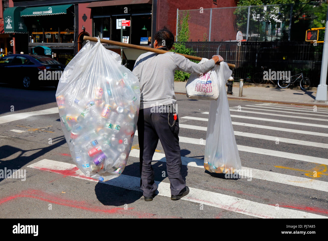A person carrying bags of recycleable bottles, and cans on a shoulder pole - Stock Image