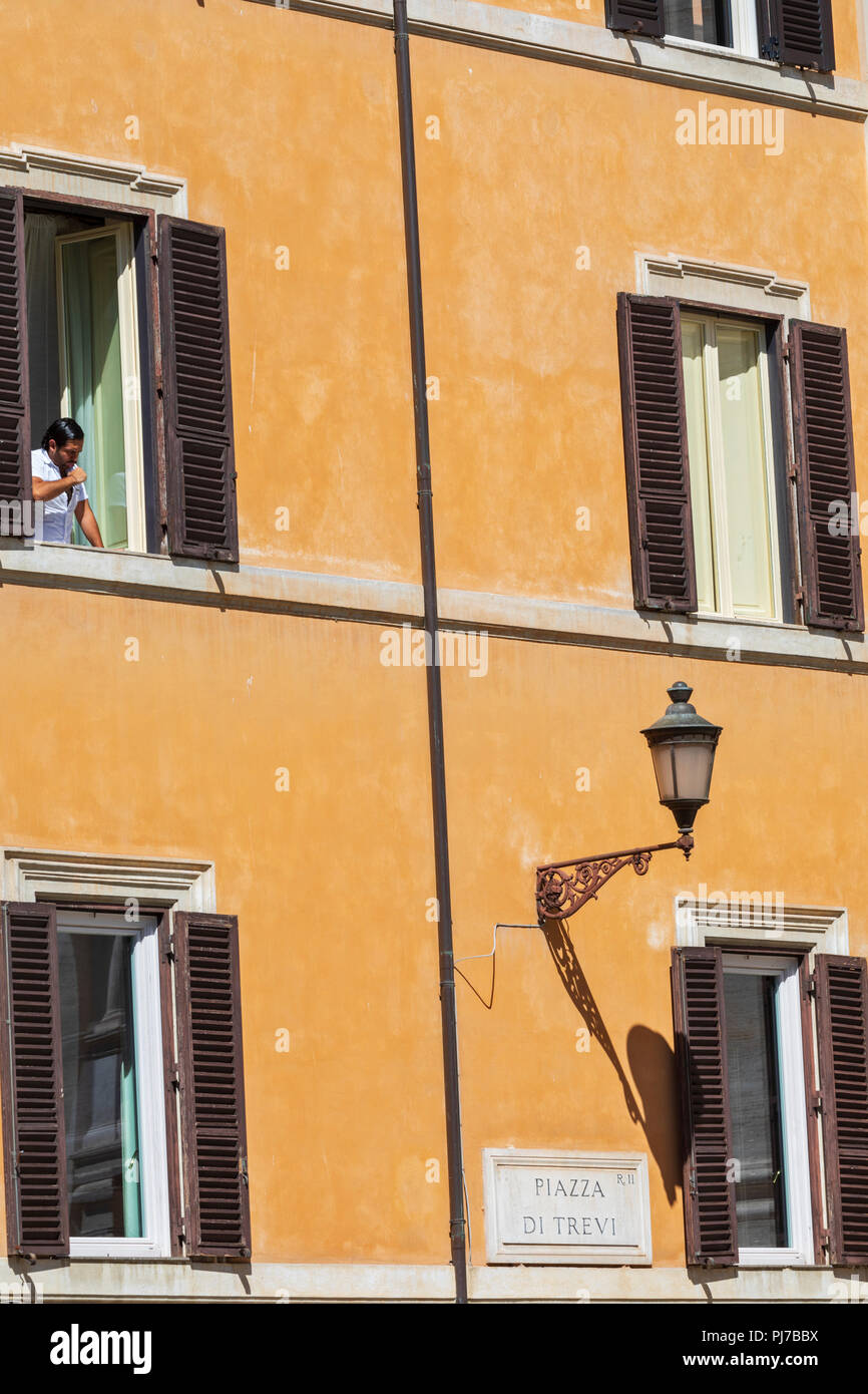 A man brushes his teeth whilst looking out from shuttered windows in Piazza di Trevi, Rome, Lazio, Italy. - Stock Image