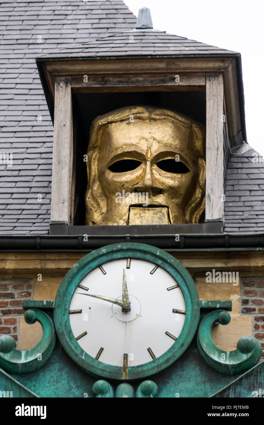 A gold theatrical face mask appears above a clock at the famous Great Puppeteer on the facade of the Institut de la Marionette ( Puppetry Institute )  - Stock Image