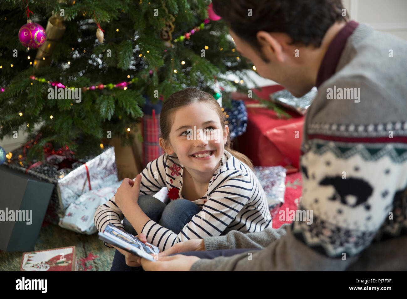 father and daughter opening christmas gifts