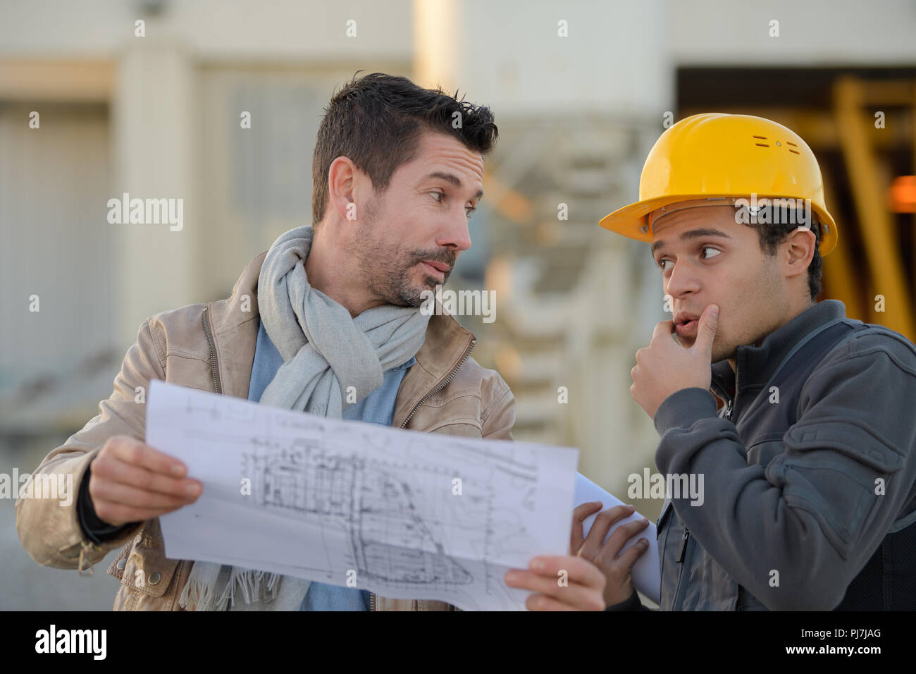male architect with worker discussing at construction site - Stock Image