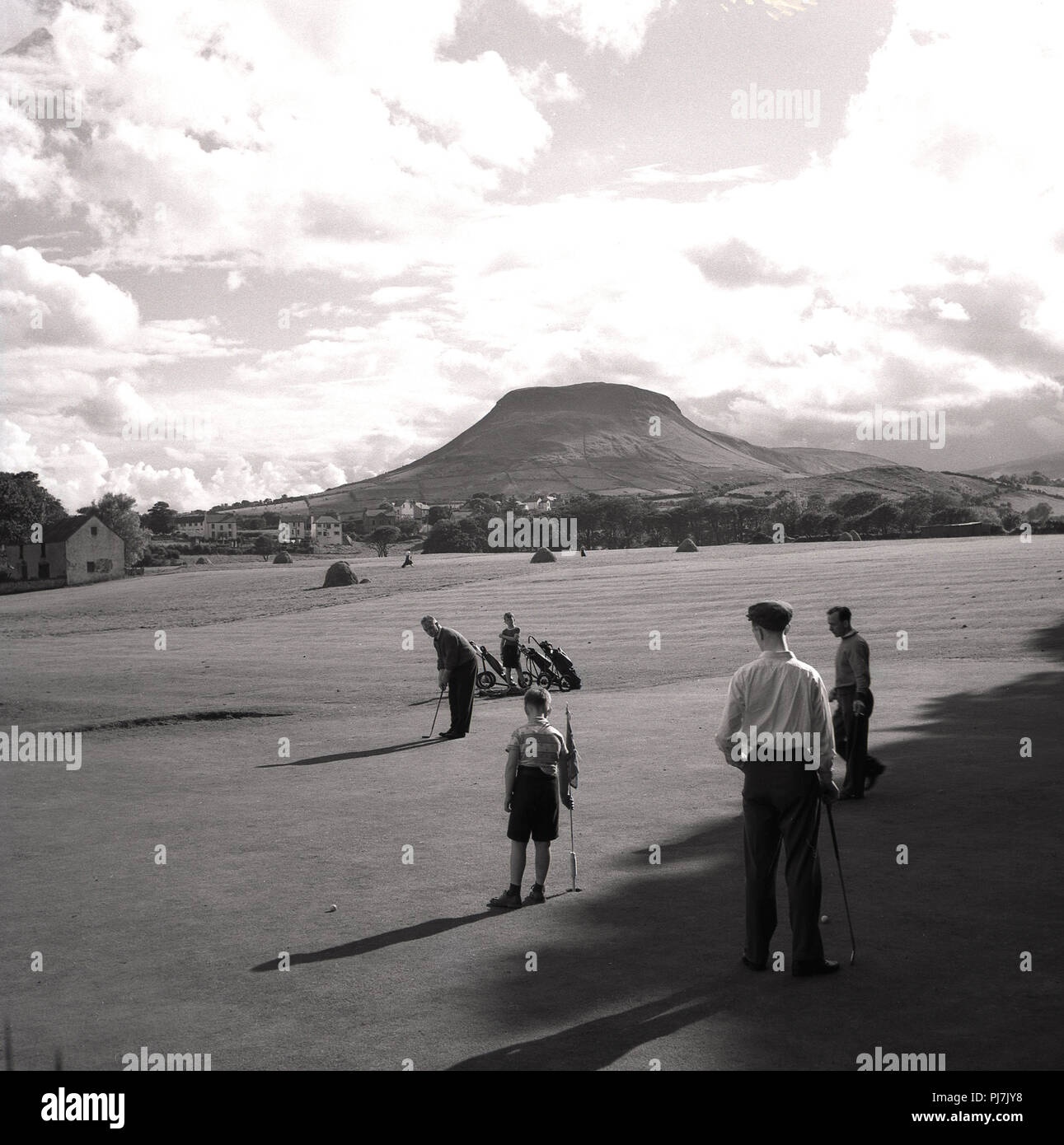1950s, golfers playing at Cushendall golf course in the beautiful setting of the Glens of Antrim, Northern Ireland, UK. - Stock Image